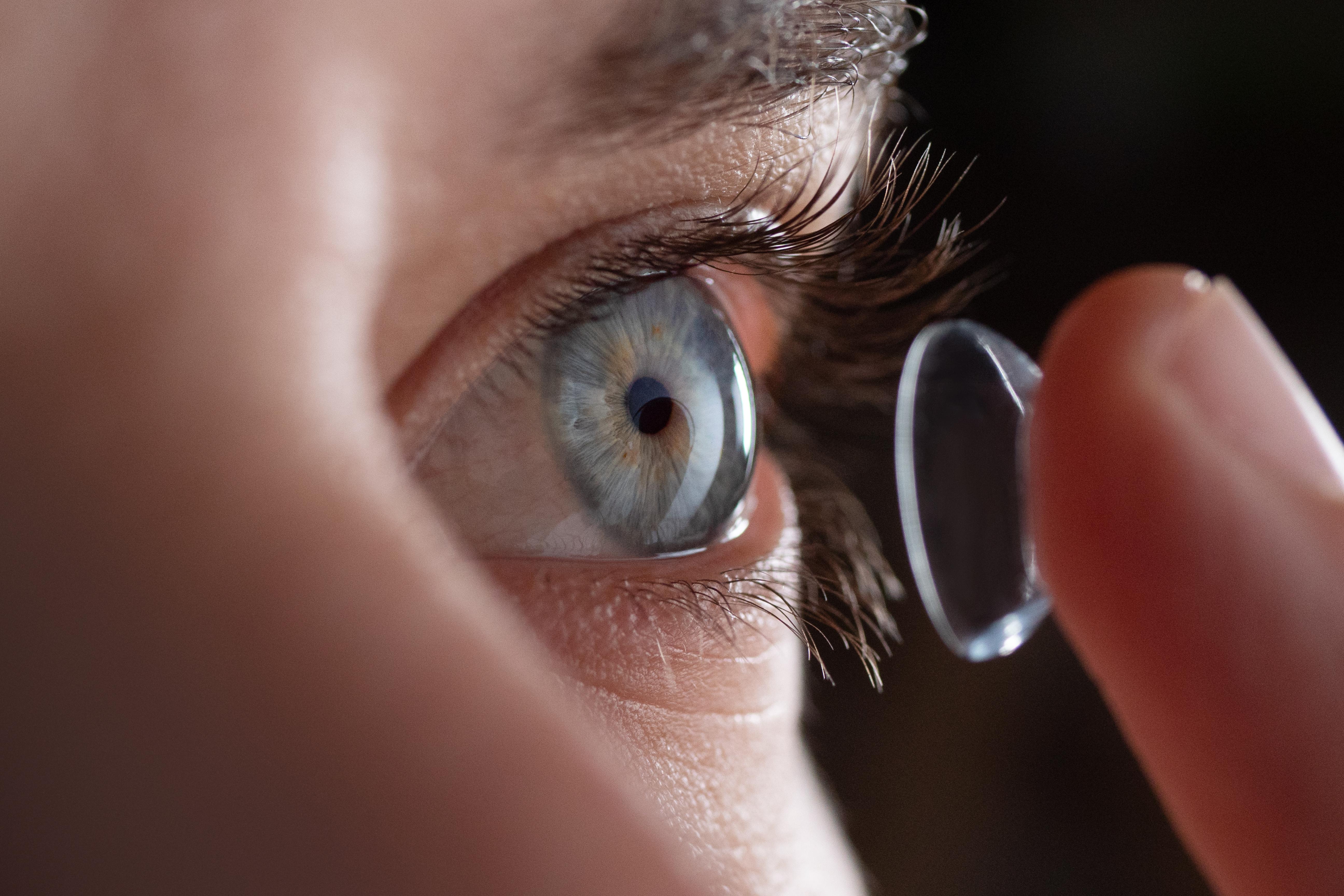 finger holding contact lens near eye