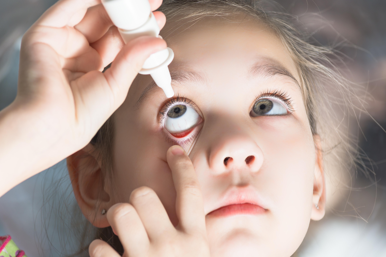 little girl using eye drops